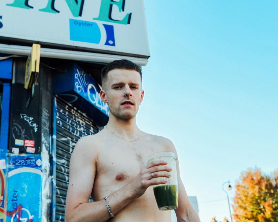 A topless man stands outside a shop during the day time holding a green smoothie
