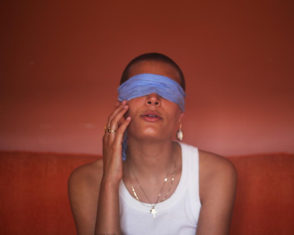 A woman in a white top sits on a red sofa in a red room with a blue blindfold over her eyes and a hand to her face