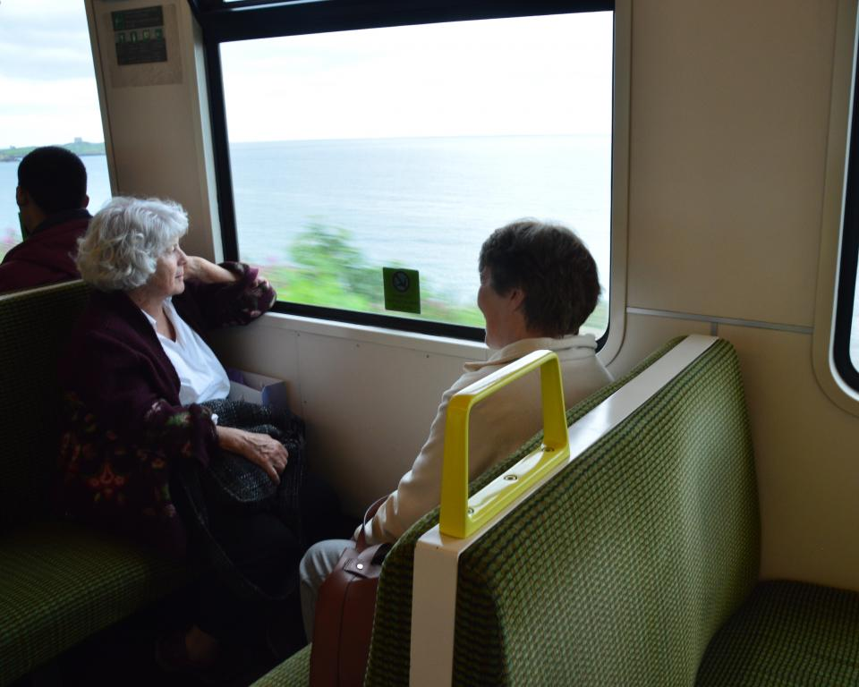 Two women sit facing each other on the dart, the one facing camera looks out the window at the sea passing by