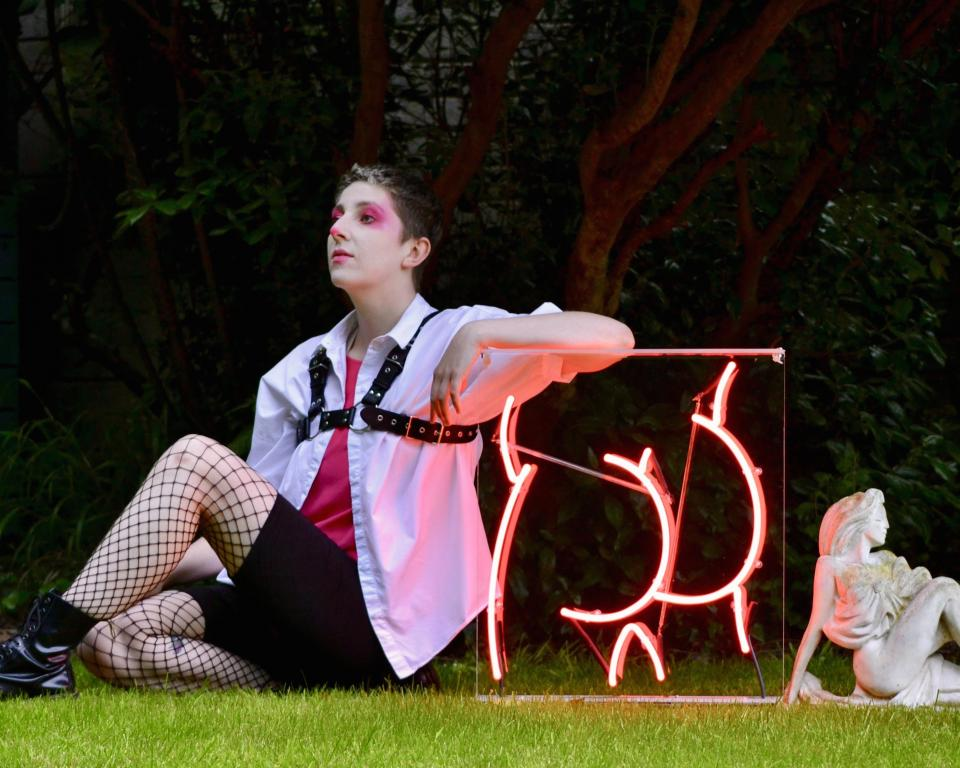 Púcaparty Glitter Hole, A woman sits on the grass leaning against a neon sign in a pose like the White Lady of Cabra statue sitting behind her