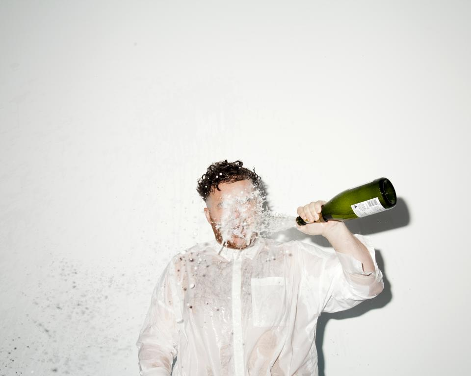 Man throwing prosecco into his face