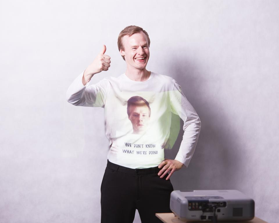 "A man smiles, giving a thumbs up, as an image of himself frowning and holding a sign saying ""We don't know what we're doing"" is projected onto his top"