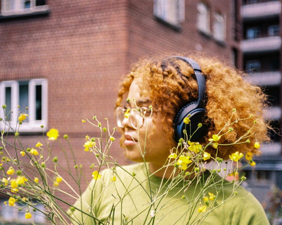 Woman with headphones by a yellow flowered bush