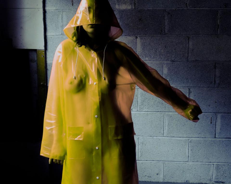 Woman in yellow hooded mac raincoat