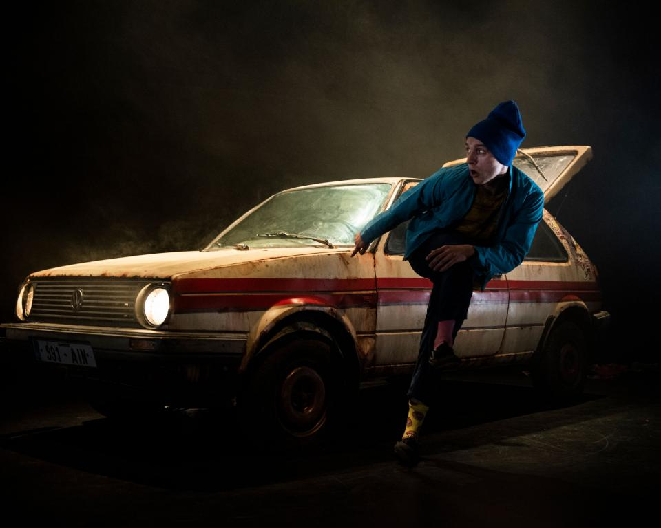 Young man dancing in front of a car with a dark background