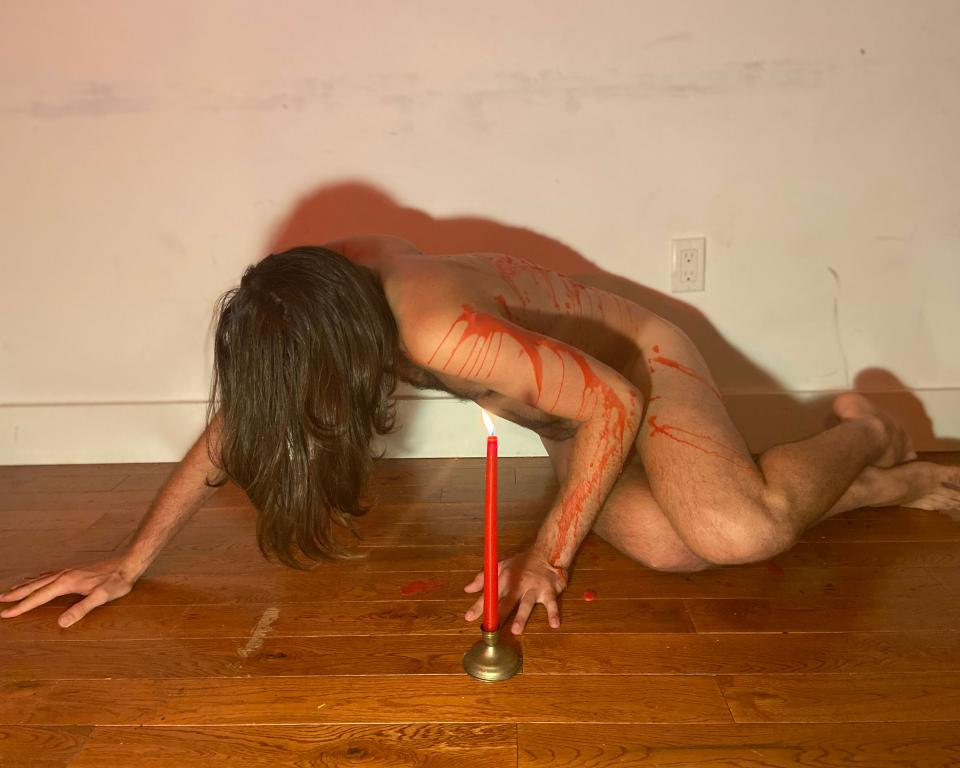 A man crouched over a wooden floor covered in red wax with a red candle in front of him