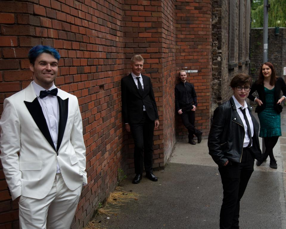 5 well dressed people stand along a red brick wall