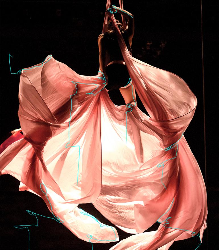 Sorry Gold, a woman hangs from an aerial silk with pink fabric billowing below her