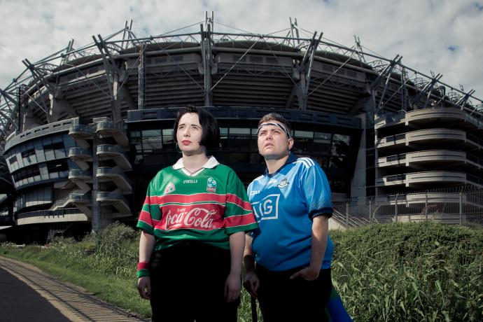 Two people stand in GAA jerseys outside of Croke Park