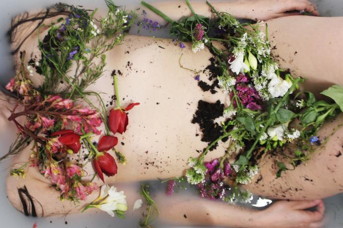 A woman's body floats in a full bath, her body covered in flowers and soil