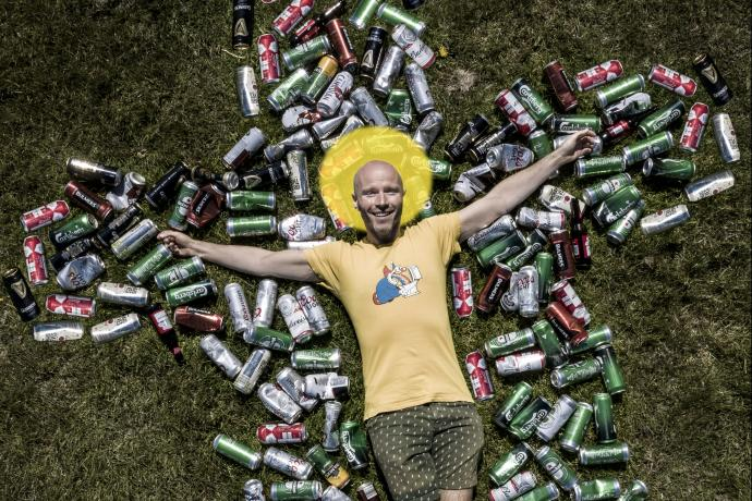 Man lying on a bed of cans in the shape of a crucifix