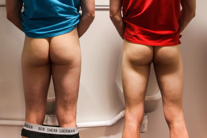 Two men stand at urinals with their trousers down