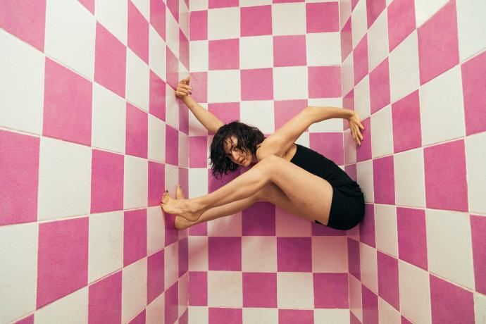 A woman in a black unitard holds herself suspended between pink and white tiled walls