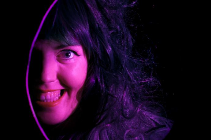 A woman's smiling face, lit in purple, is visible through a oval hole in a black space