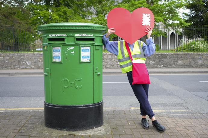 Postwoman holding a heart envelope beside an Irish postbox