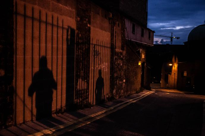The shadows of two people, standing apart against railings, are projected onto an alley wall at night