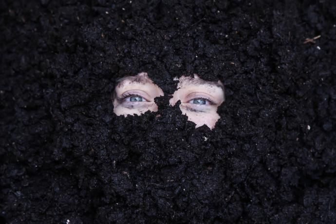 A face buried in the dirt so that only the eyes are visible