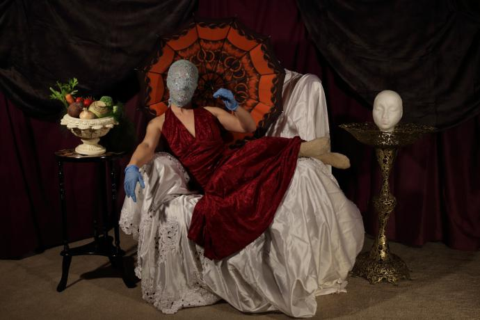 Woman in red dress wearing a mask, lounging on a chair