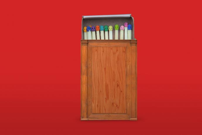 A wooden matchbox, reminiscent of a judge's bench, filled with multicoloured matches lies against a red background