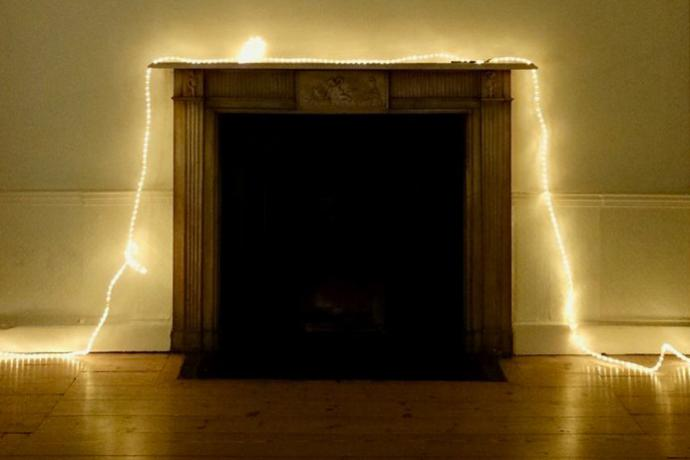 A dark fireplace is draped with a line of fairy lights that continues across the floor on either side of it in a beige room with wood floors
