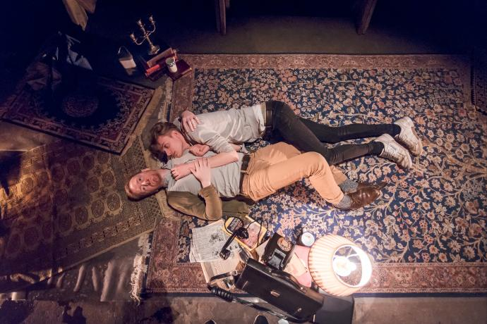 Two men lie together on a carpet holding each other