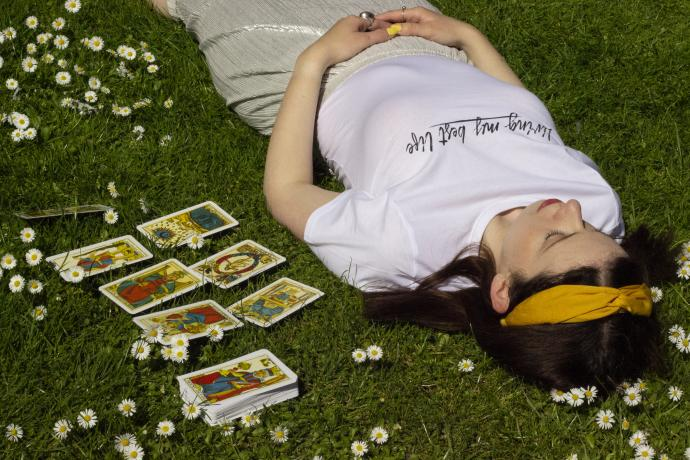 A woman lies on the grass surrounded by daisies with a deck of tarot and a tarot spread laid out next to her
