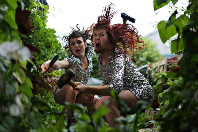 Two fierce women in sequin dresses crouch with garden weapons in leafy surroundings