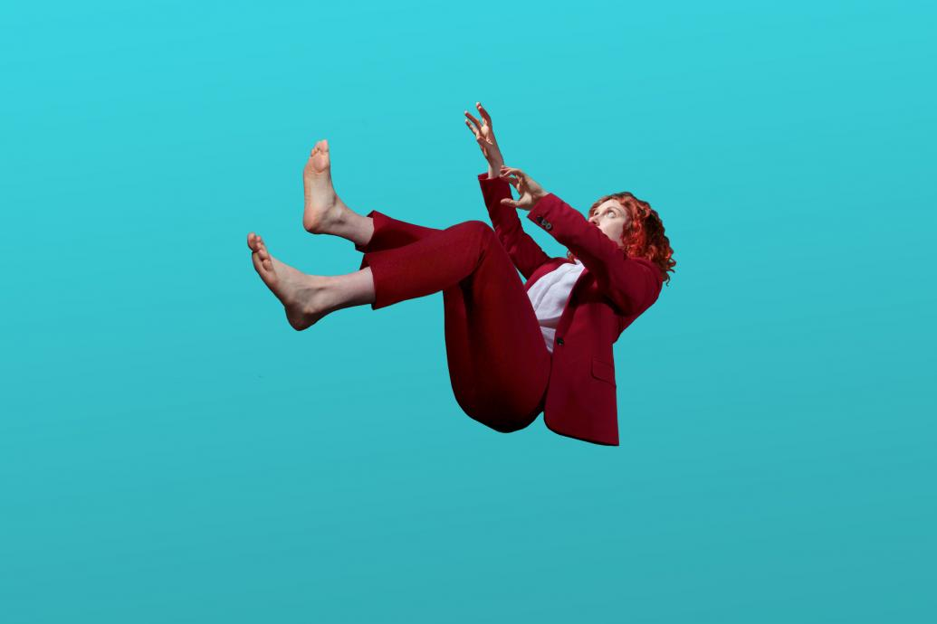 A barefoot woman in a red suit falls through a pure blue space