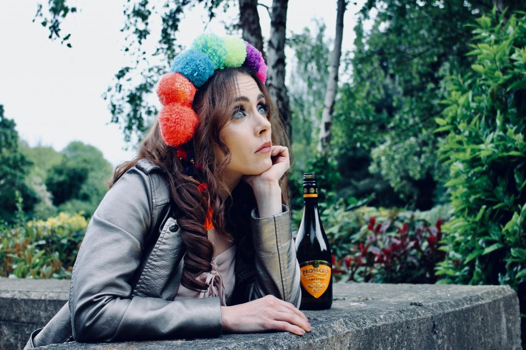 Modern Juliette in flower crown and biker jacket looking out wistfully from a balcony window, with a Buckfast beside her.