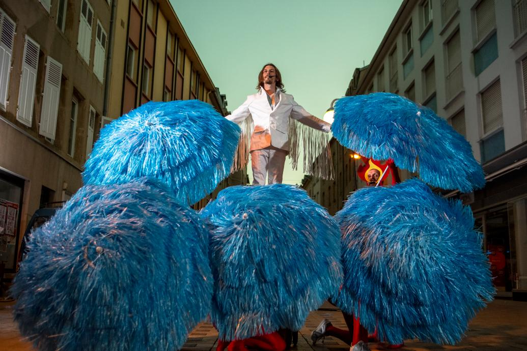 A man dressed in a white suit with fringed sleeves stands on top of a group of umbrellas covered in blue tinsel held by people wearing flame headdresses