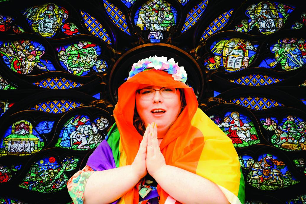 A woman poses against a stained glass window like the Virgin Mary, her hands held in prayer, her veil is a Pride flag and she wears a flower crown