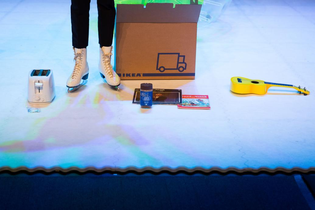 A person stands in ice-skates on an ice rink, only their feet and calves are visible, to the left is a toaster, to the right an Ikea box, a jar of coffee, a record, a book and a ukulele