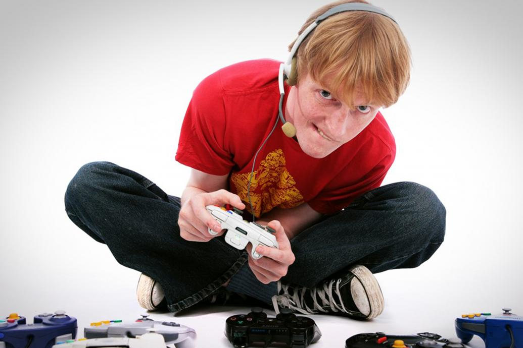 A man sits on the ground in a white room with a headset on, surrounded by game controllers on the floor, as he holds one in both hands