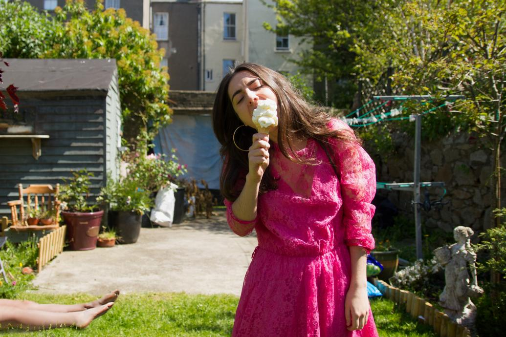 Woman eating an ice-cream, with a body in the background