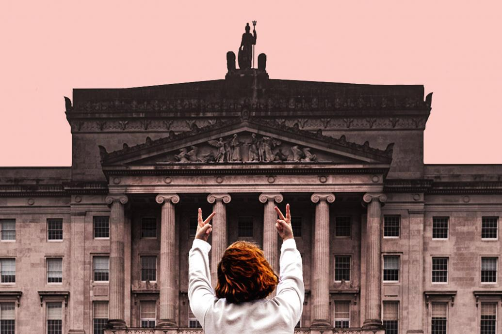 A woman with her back to camera faces Stormont, giving it two fingers up with both hands held up
