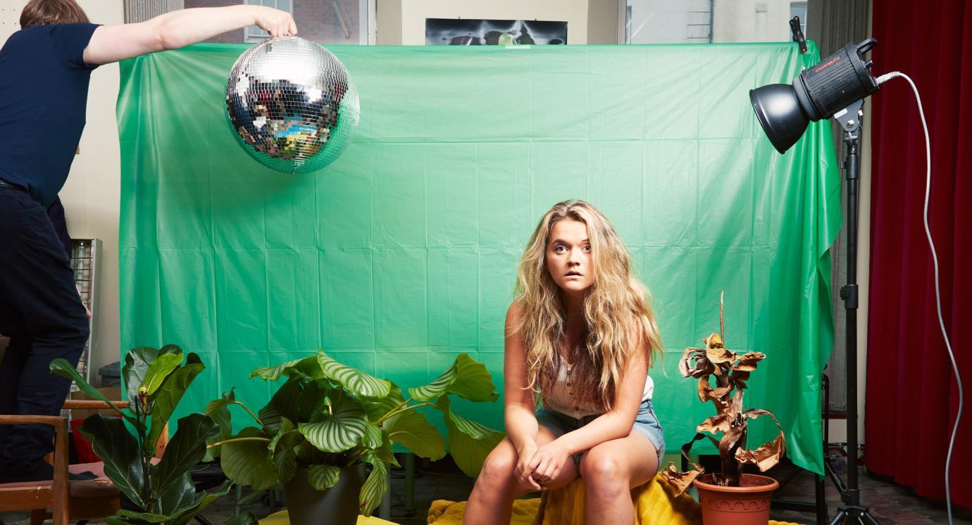 Woman sitting by green screen surrounded by props of plants and a disco ball held in the air by a man